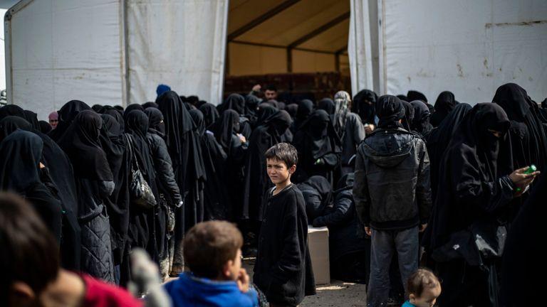 Des réfugiées irakiennes et des femmes syriennes déplacées vivant dans le camp d'al-Hol abritant des membres de la famille d'un membre de l'État islamique (IS), font la queue pour recevoir des marchandises dans le camp situé dans le gouvernorat d'al-Hasakeh, dans le nord-est de la Syrie, le 28 mars 2019.