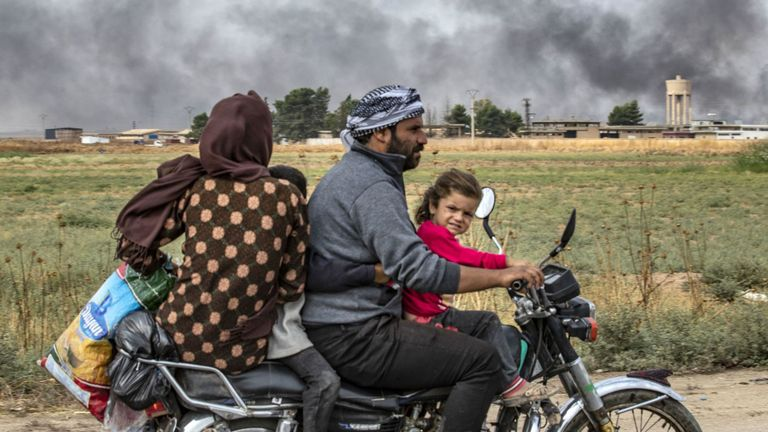 """Des membres d'une famille syrienne utilisent une moto pour fuir la campagne de la ville de Ras al-Ain au nord-est de la Syrie, à la frontière turque, en direction de l'ouest de la ville de Tal Tamr, le 19 octobre 2019. La fumée derrière eux provient de pneus en feu. utilisé pour gêner la visibilité des avions de guerre. - Le président turc Recep Tayyip Erdogan a lancé un nouvel avertissement aujourd'hui pour """"écraser"""" les forces kurdes alors que les deux parties échangeaient des accusations de violation du traité de trêve négocié par les États-Unis dans le nord-est de la Syrie. (Photo par Delil SOULEI"""