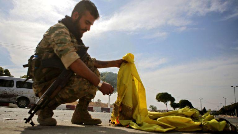 Un combattant syrien soutenu par la Turquie a brûlé le drapeau des Forces démocratiques syriennes (SDF) dans la ville d'Ayn al-Arus, au sud de la ville frontalière de Tal Abyad, le 14 octobre 2019, alors que la Turquie et ses alliés poursuivent leur assaut Villes frontalières tenues par les Kurdes dans le nord-est de la Syrie. - Les forces du régime syrien se sont dirigées vers la frontière turque après la conclusion d'un accord entre Damas et les forces kurdes assiégées à la suite d'une annonce du retrait américain, ont rapporté les correspondants de l'AFP. (Photo de Bakr ALKASEM / AFP) (Photo de