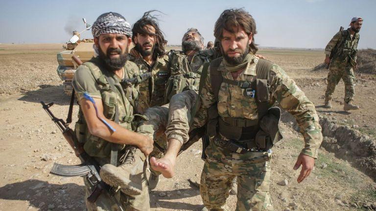 Des rebelles syriens soutenus par la Turquie transportent un combattant blessé alors qu'ils combattaient des Kurdes syriens dans la ville frontalière de Tal Abyad