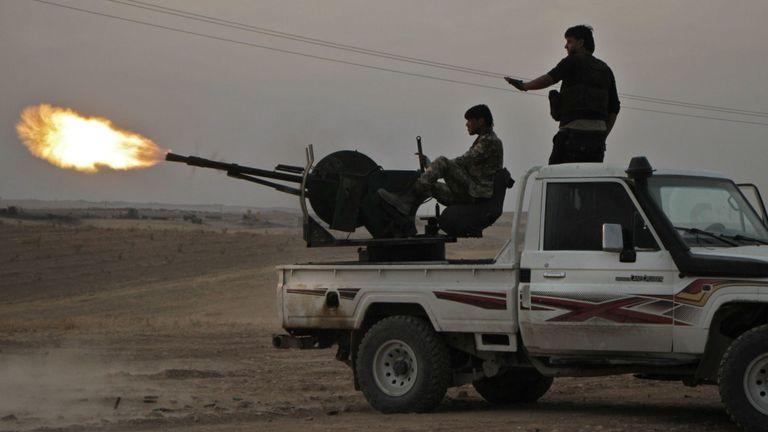 Des combattants syriens soutenus par la Turquie tirent un poids lourd monté sur un camion près de la ville de Tukhar, au nord de la ville de Manbij, dans le nord de la Syrie, le 14 octobre 2019, alors que la Turquie et ses alliés poursuivent leurs assauts contre le Kurdistan- tenu des villes frontalières dans le nord de la Syrie. - La Turquie souhaite créer une zone tampon d'environ 30 kilomètres le long de sa frontière pour tenir les forces kurdes à distance et renvoyer une partie des 3,6 millions de réfugiés syriens qu'elle accueille. (Photo par Aref TAMMAWI / AFP) (Photo par AREF TAMMAWI / AFP vi