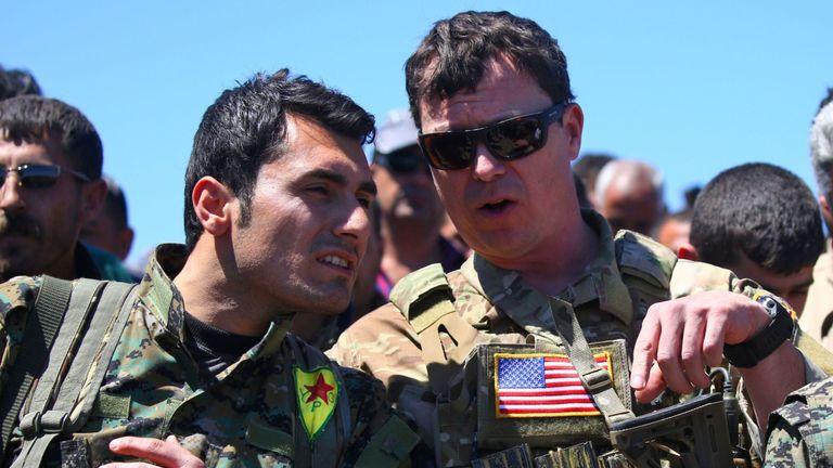 Un officier américain s'entretient avec un combattant des unités de protection du peuple kurde près de la ville de Derik, dans le nord-est de la Syrie.