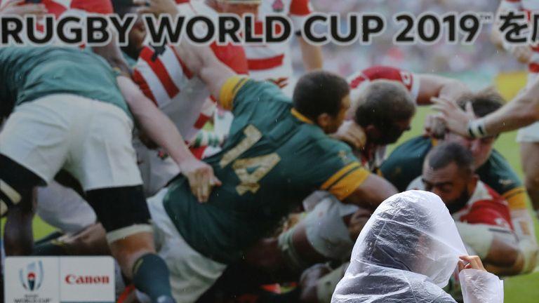 Une femme passe devant un panneau publicitaire de la Coupe du monde de rugby dans le Shinagawa