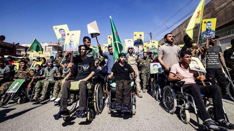 Des combattants kurdes ont tenu des photos de camarades morts alors qu'ils marchaient pour protester contre l'action militaire turque