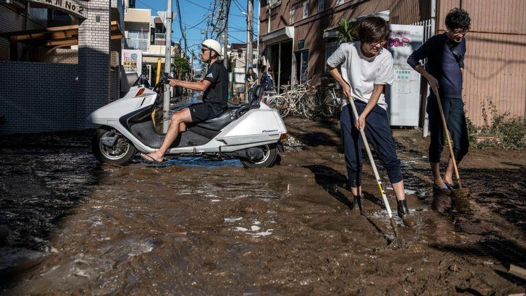 Des personnes évacuent la boue de leurs maisons après avoir été inondées lors du typhon Hagibis, le 13 octobre 2019 à Kawasaki, au Japon.