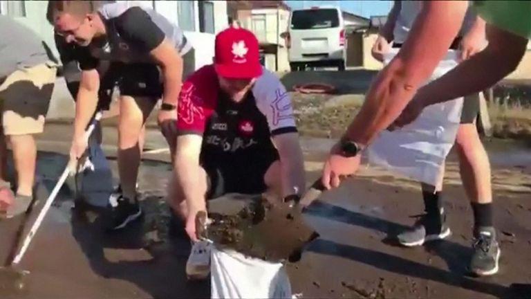 Les joueurs canadiens sont descendus dans les rues pour pelleter la boue et nettoyer les débris après le passage de la tempête.