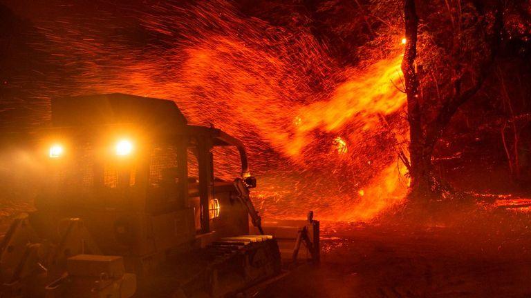 Les braises s'envolent d'un arbre alors qu'un bulldozer se préparait à combattre le feu près de Geyserville