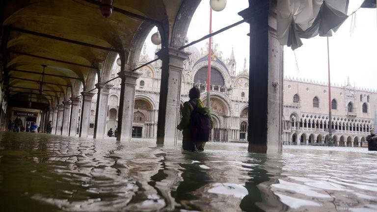 Une personne traverse une arcade inondée près de la basilique Saint-Marc