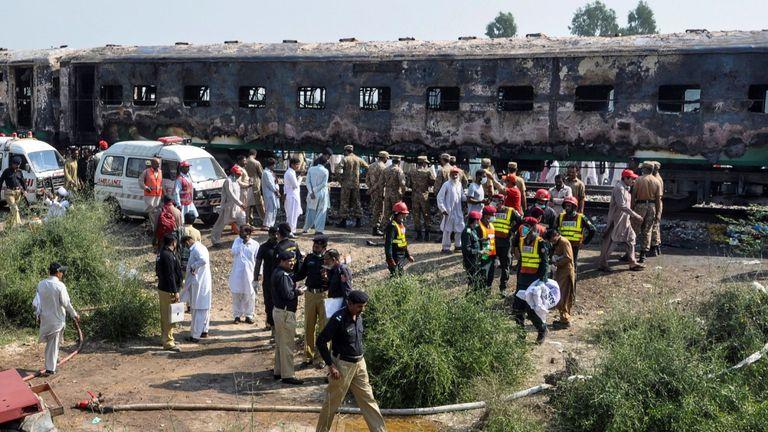 Les pompiers travaillent pour calmer les wagons brûlés après l'incendie d'un train de passagers qui a pris feu près de Rahim Yar Khan dans la province du Punjab le 31 octobre 2019