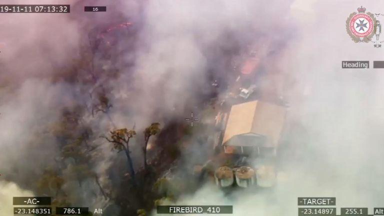 La fumée engloutit une propriété suite à la propagation de feux de brousse dans le Queensland, en Australie, le 11 novembre 2019. Photo prise le 11 novembre 2019. Photo: Services d'incendie et d'urgence à Queensland