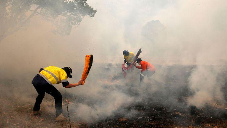 Des habitants tentent de supprimer les incendies, d'un feu de brousse, en se dirigeant vers une maison située sur une propriété à Koorainghat, près de Taree, dans la région de la côte nord du NSW, en Australie, le 12 novembre 2019.