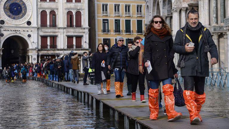 Les touristes utilisent une plate-forme temporaire pour traverser la place Saint-Marc.