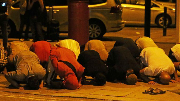 Les hommes prient après qu'une camionnette entre en collision avec des piétons près d'une mosquée dans la région de Finsbury Park