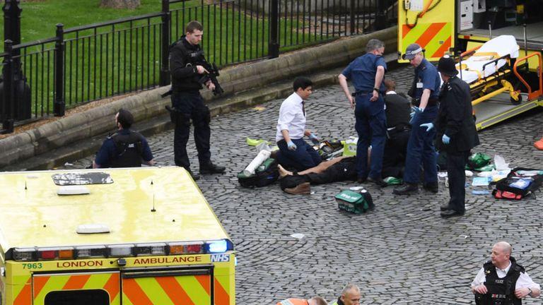 Les services d'urgence assistent à un homme devant le palais de Westminster