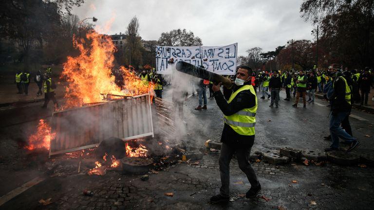 TOPSHOT - Les manifestants construisent une barricade lors d'une manifestation des Gilets jaunes (Gilets jaunes) contre la hausse des prix du pétrole et du coût de la vie, le 1er décembre 2018 à Paris. (Photo par Abdulmonam EASSA / AFP) (Le crédit photo doit se lire ABDULMONAM EASSA / AFP via Getty Images)