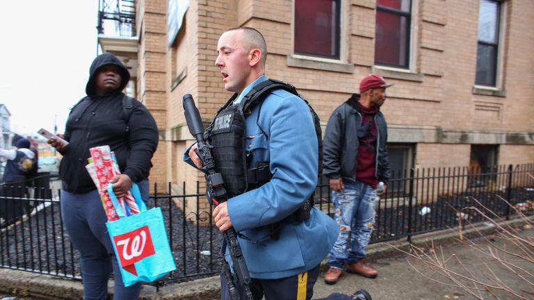 Des policiers arrivent sur les lieux d'un tireur actif à Jersey City, New Jersey, le 10 décembre 2019. - Un officier a été abattu lorsque deux hommes armés avec un long fusil ont ouvert le feu à Jersey City, New Jersey, dans l'après-midi du 10 décembre. , 2019, selon deux responsables. Deux suspects ont été barricadés dans un dépanneur, ont indiqué les responsables. Un officier était emmené dans un hôpital voisin. (Photo par Kena Betancur / AFP) (Photo par KENA BETANCUR / Afp / AFP via Getty Images)