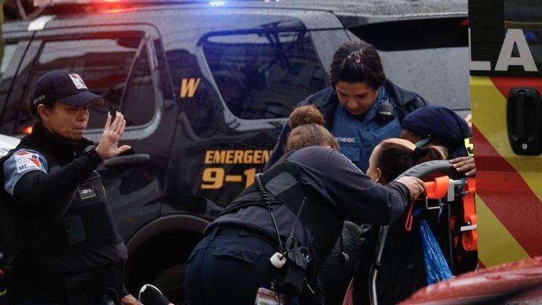 Une femme reçoit des soins médicaux sur les lieux d'une fusillade active à Jersey City le 10 décembre 2019. - Un officier a été abattu lorsque deux hommes armés avec un long fusil ont ouvert le feu à Jersey City (New Jersey) dans l'après-midi du 10 décembre. 2019, selon deux responsables. Deux suspects ont été barricadés dans un dépanneur, ont indiqué les responsables. Un officier était emmené dans un hôpital voisin. (Photo par Kena Betancur / AFP) (Photo par KENA BETANCUR / Afp / AFP via Getty Images)