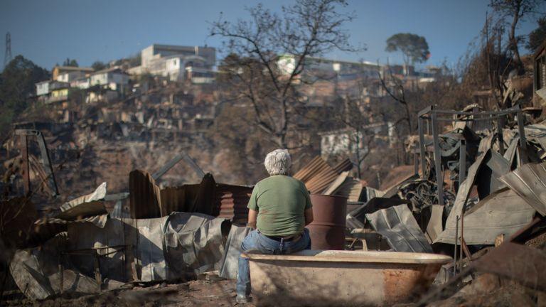 TOPSHOT - Un homme examine la destruction causée par un incendie de forêt sur la colline Rocuant à Valparaiso, au Chili, le 25 décembre 2019. - Plus de 100 maisons ont été touchées par un incendie de forêt mardi à Valparaiso, où une alerte rouge a été déclarée. (Photo de Pablo Rojas Maradiaga / AFP) (Photo de PABLO ROJAS MARADIAGA / AFP via Getty Images)