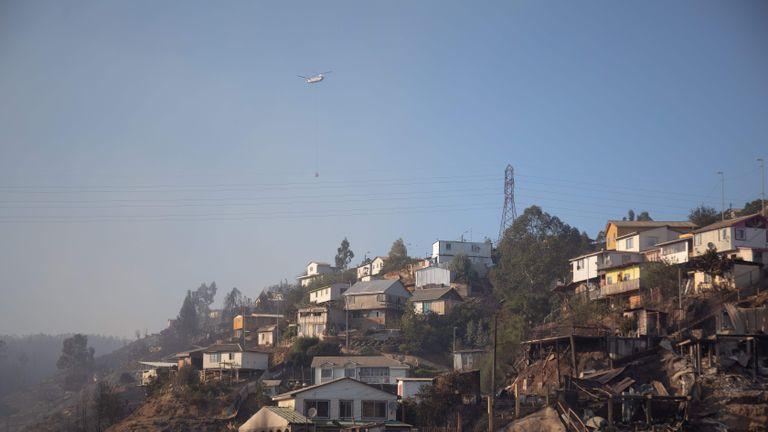 Un hélicoptère transporte de l'eau pour éteindre un incendie de forêt près de la colline Rocuant à Valparaiso, au Chili, le 25 décembre 2019. - Plus de 100 maisons ont été touchées par un incendie de forêt mardi à Valparaiso, où une alerte rouge a été déclarée. (Photo de Pablo Rojas Maradiaga / AFP) (Photo de PABLO ROJAS MARADIAGA / AFP via Getty Images)