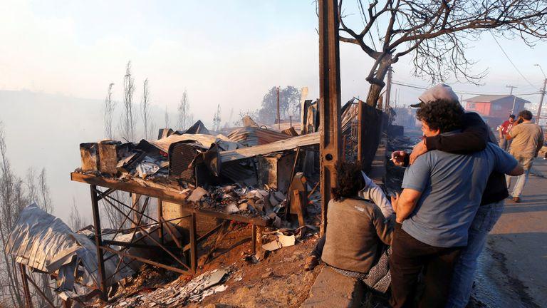 Les gens réagissent à côté des débris de leur maison après la propagation des incendies de forêt à Valparaiso, au Chili, le 24 décembre 2019. REUTERS / Rodrigo Garrido