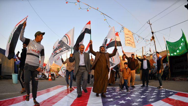 Les Irakiens marchent sur un drapeau national américain le 30 décembre 2019, lors d'une manifestation pour dénoncer les attaques de la nuit précédente par des avions américains sur plusieurs bases appartenant aux brigades du Hezbollah près d'Al-Qaim, un district irakien limitrophe de la Syrie. - Les frappes aériennes américaines contre un groupe pro-iranien en Irak auraient tué au moins 25 combattants, déclenchant la colère dans un pays pris dans les tensions croissantes entre Téhéran et Washington. (Photo de Haidar HAMDANI / AFP) (Photo de HAIDAR HAMDANI / AFP via Getty Images)