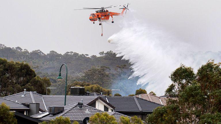 Une grue skycrane laisse tomber l'eau sur un feu de brousse en broussailles derrière les maisons à Bundoora, Melbourne