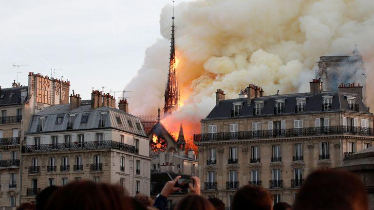 Les spectateurs sont sous le choc alors que la flèche au sommet de la cathédrale Notre-Dame s'effondre dans un incendie.