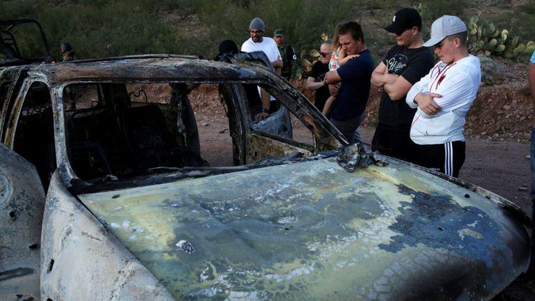 Des proches de membres tués de familles mexico-américaines appartenant à des communautés mormones observent l'épave brûlée d'un véhicule où certains de leurs proches sont morts, à Bavispe, dans l'État de Sonora, au Mexique, le 5 novembre 2019