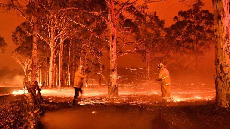 Cette image à exposition temporisée montre des pompiers arrosant des arbres alors qu'ils luttent contre les feux de brousse autour de la ville de Nowra dans l'État australien de la Nouvelle-Galles du Sud le 31 décembre 2019
