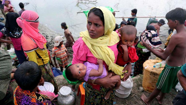Une réfugiée rohingya de Buthidaung porte ses enfants après avoir traversé la rivière Naf avec un radeau improvisé pour atteindre le Bangladesh