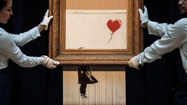 Les employés de Sotheby posent avec & quot; L'amour est dans le bac & quot; par Banksy