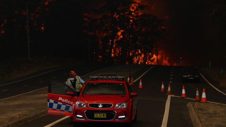 Un officier de police de la Nouvelle-Galles du Sud se prépare à fuir son barrage routier sur la Princes Highway près de la ville de Sussex Inlet le 31 décembre 2019 à Sydney, Australie