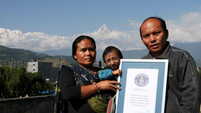 Le Népalais Khagendra Thapa Magar (C), le plus petit homme du monde, pose avec ses parents Rup Bahadur Thapa Magar (R) et sa mère Dhana Maya Thapa (L) tout en tenant son certificat d'enregistrement Guiness dans le contexte du mont Machchhapuchhre à leur domicile à Pokhara, à environ 200 km à l'ouest de Katmandou, le 29 octobre 2010. Magar a été officiellement reconnu comme l'homme le plus petit du monde par le Livre Guinness des records le 14 octobre 2010 à l'âge de 18 ans. Khagendra Thapa Magar ne mesure que 67,48 centimètres (26,4 pouces) grand, selon les mesures finales prises par Guinness World Records. AFP PHOTO / Prakash MATHEMA (Le crédit photo doit se lire PRAKASH MATHEMA / AFP via Getty Images)