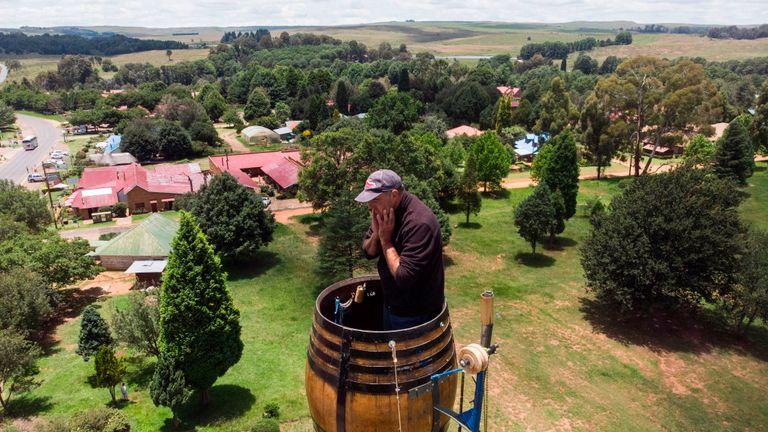 Une vue aérienne montre Vernon Kruger, 52 ans, tenant son visage tout en se tenant dans un tonneau au sommet d'un poteau à 25 mètres au-dessus du sol à Dullstroom le 16 janvier 2020. - Vernon Kruger est sur le point de battre un record du monde Guinness établi par lui-même en 1997 où il est resté en pole pendant 54 jours. Il a commencé sa nouvelle tentative le 14 novembre 2019 et d'ici le 20 janvier 2020, Kruger atteindra son objectif de passer 64 jours assis en pole. (Photo par ANTOINE DEMAISON / AFP) (Photo par ANTOINE DEMAISON / AFP via Getty Images)