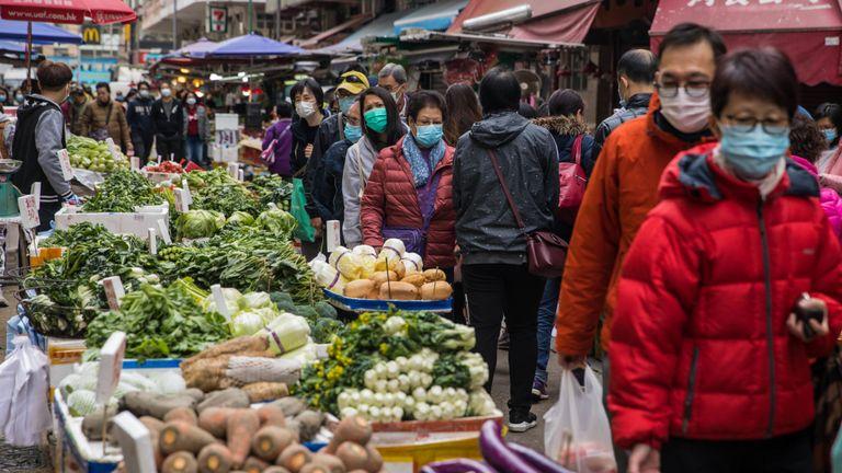 Les acheteurs de Hong Kong portent des masques alors que le gouvernement ferme certaines parties de la frontière avec la Chine