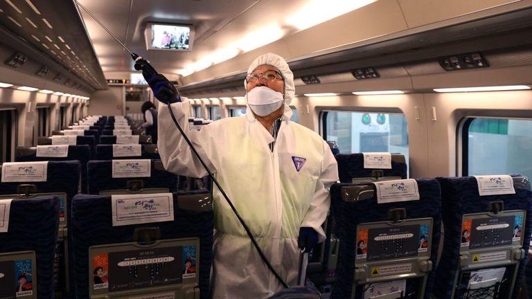 Un travailleur de la désinfection portant des engrenages de protection pulvérise une solution anti-septique dans un train à Séoul, Corée du Sud
