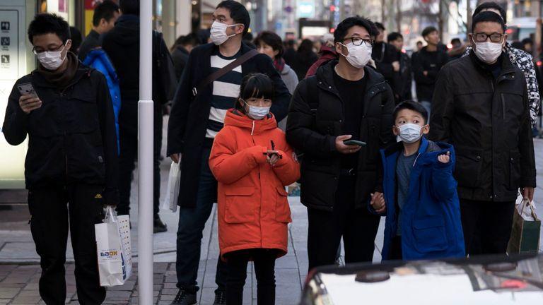 Les touristes chinois portant des masques traversent le quartier commerçant de Ginza à Tokyo, Japon