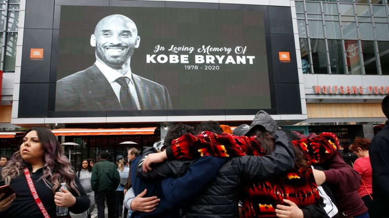 Les fans se rassemblent près d'une image de Kobe Bryant affichée sur un grand écran à l'extérieur du Staples Center, LA