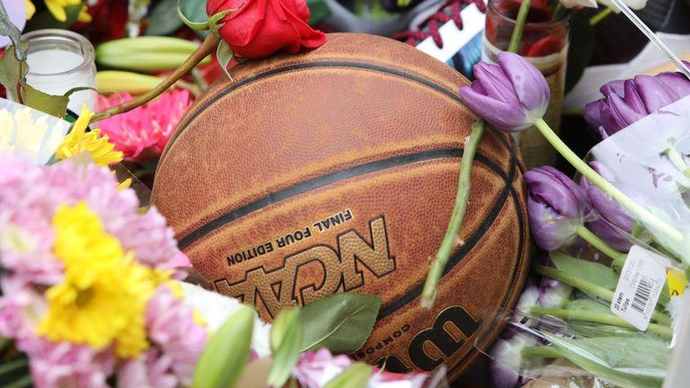 Un ballon de basket se trouve au milieu des fleurs dans un sanctuaire de fortune au Staples Center à Los Angeles /