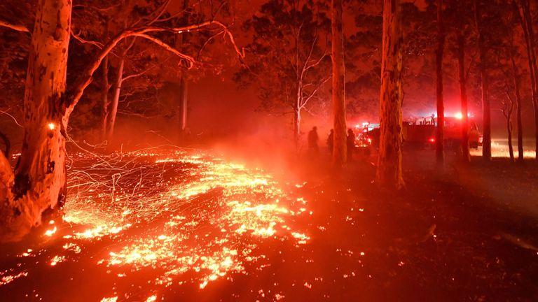 Des braises brûlantes couvrent le sol alors que les pompiers (à l'arrière R) luttent contre les feux de brousse autour de la ville de Nowra dans l'État australien de la Nouvelle-Galles du Sud le 31 décembre 2019