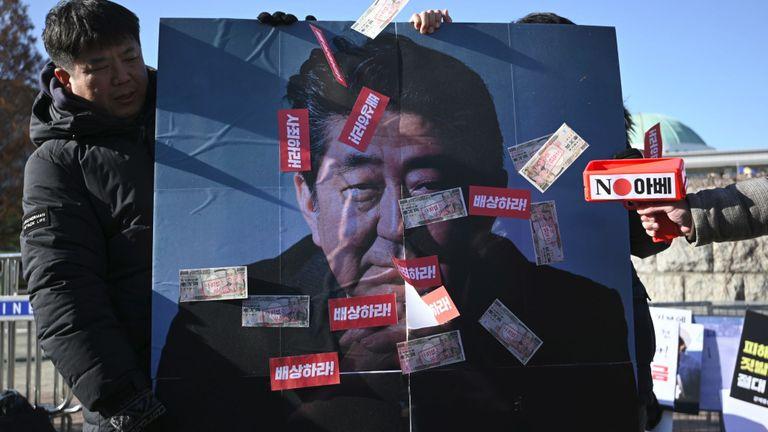Des manifestants sud-coréens tiennent une bannière montrant une photo du Premier ministre japonais Shinzo Abe