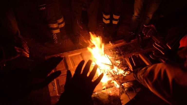 Les autorités et la police turques tentent de se réchauffer sur les lieux d'un immeuble effondré