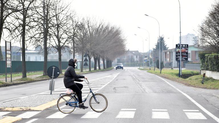 Une personne portant un masque facial fait du vélo dans la ville de Codogno, qui a été fermée par le gouvernement italien en raison d'une épidémie de coronavirus dans le nord de l'Italie, le 23 février 2020. REUTERS / Flavio Lo Scalzo