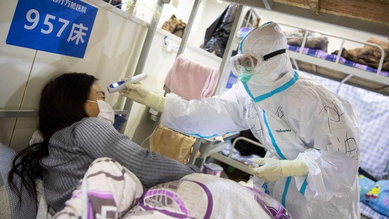 Le personnel médical vérifie la température d'un patient présentant des symptômes légers de COVID-19 dans un centre d'exposition transformé en hôpital à Wuhan
