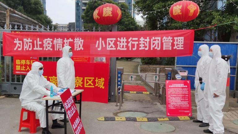Les travailleurs en tenue de protection enregistrent les résidents et prennent leur température dans un lotissement à Wuhan