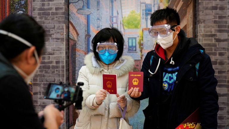 Su, 28 ans (L) et Jia, 29 ans, se sont mariés - portant des masques faciaux - dans un bureau d'enregistrement le jour de la Saint-Valentin à Shanghai