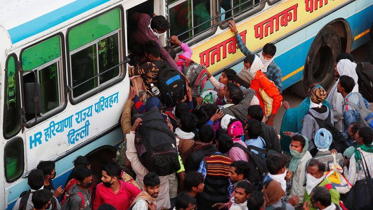 Les travailleurs migrants montent à bord des bus