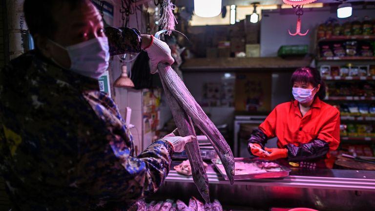 Un homme portant un masque facial tient un poisson dans un marché de Wuhan, dans la province centrale du Hubei, en Chine, le 7 avril 2020. - Wuhan, la ville du centre de la Chine où le coronavirus a fait son apparition l'année dernière, a en partie rouvert le 28 mars après plus de deux mois d'isolement quasi total pour sa population de 11 millions d'habitants. (Photo par Hector RETAMAL / AFP) (Photo par HECTOR RETAMAL / AFP via Getty Images)
