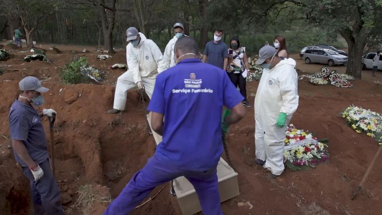 Les ouvriers du cimetière abaissent un cercueil dans une tombe