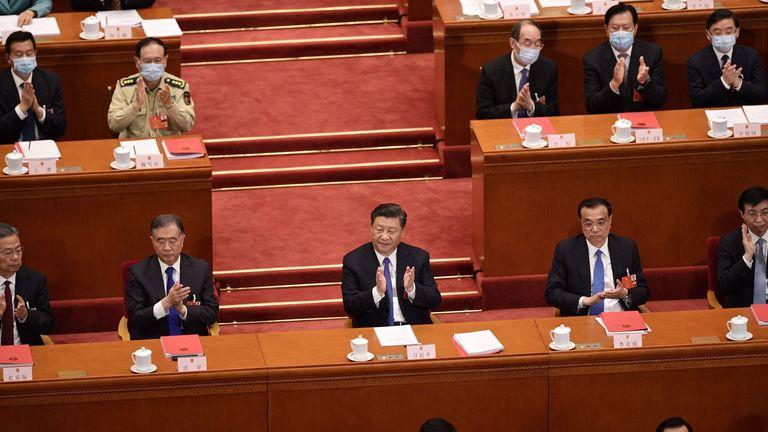 Le président chinois Xi Jinping (C) applaudit après que le Congrès national du peuple a approuvé une proposition de rédaction d'une loi sur la sécurité à Hong Kong